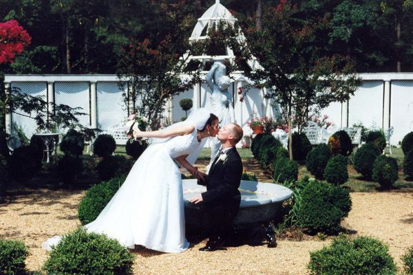 Bride kissing groom during wedding in front of gazebo